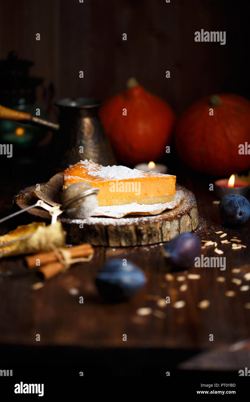 Piece of pumpkin cheesecake with powdered sugar, plums, pumpkins, table lamp on a dark wooden background - Stock Image