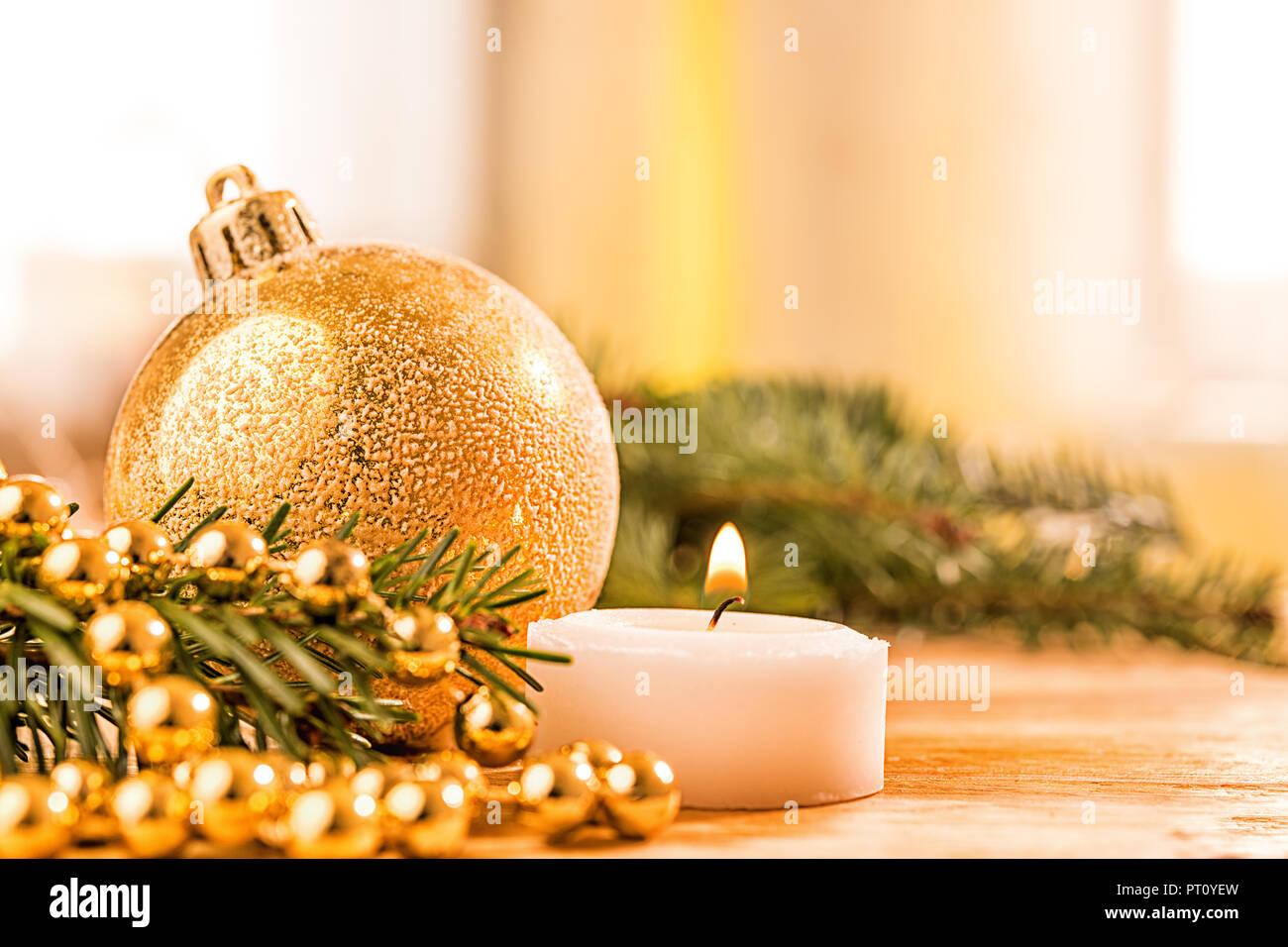 Goldene christbaumkugel mit Tannenzweig, Kerze,  Lichter und Deko - Stock Image