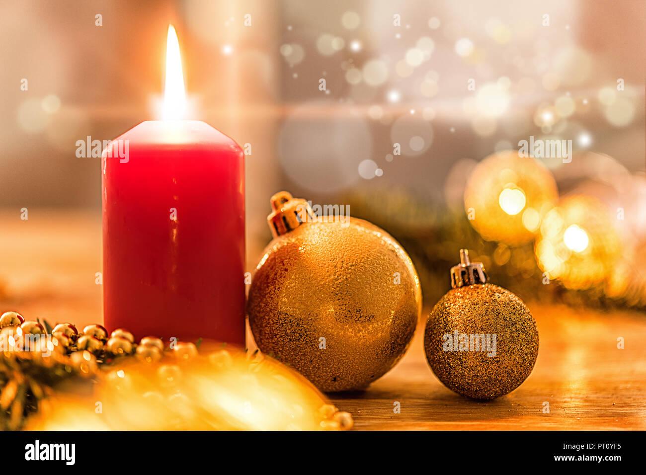 Goldene christbaumkugel mit Tannenzweig, Kerze,  Lichter und Deko Stock Photo