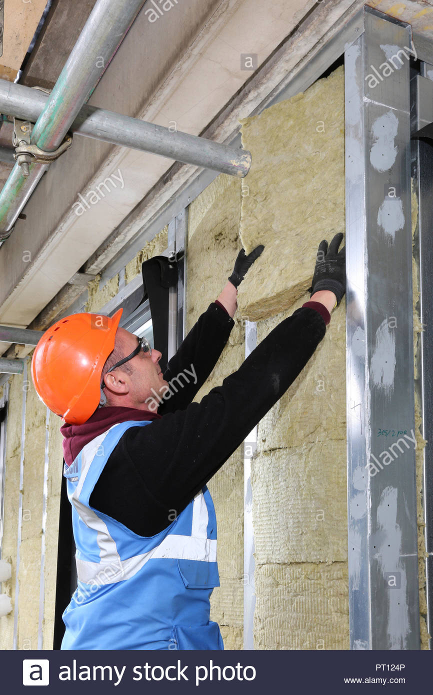 A workman installs fireproof mineral wool insulation as part of the over-cladding of a London council apartment block. - Stock Image