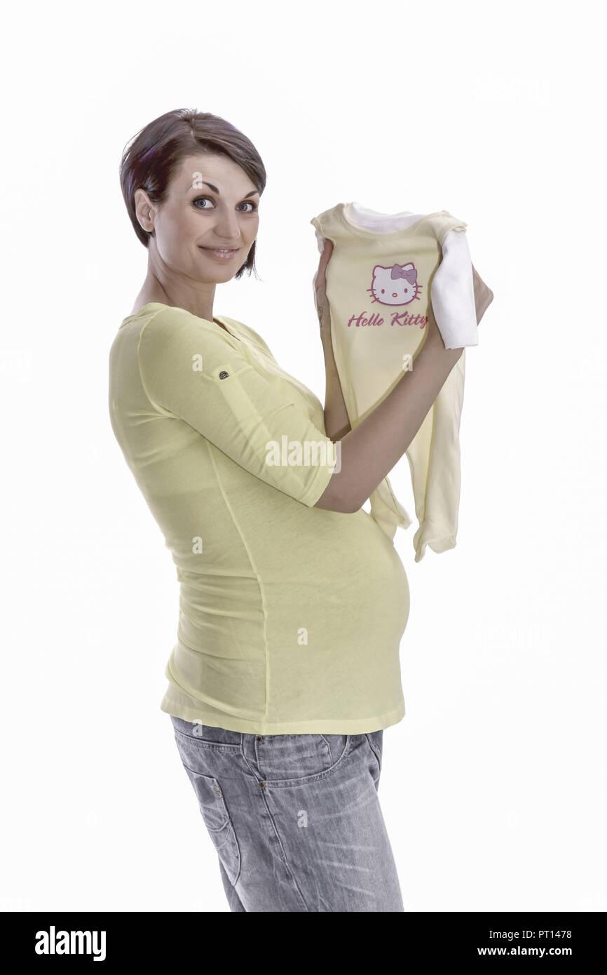 Schwangere Frau in freudiger Erwartung zeigt Babybekleidung (model-released) - Stock Image