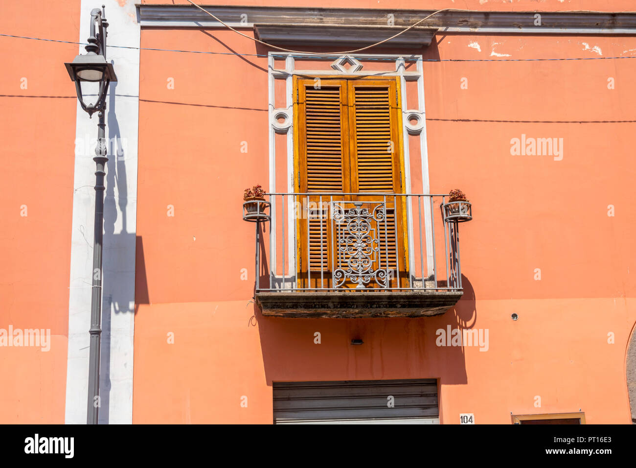 Traditional Italian door with shutters, metal balcony Italy, orange brown wall over shop, old fashioned concept, ornate,  wooden shutter doors Stock Photo