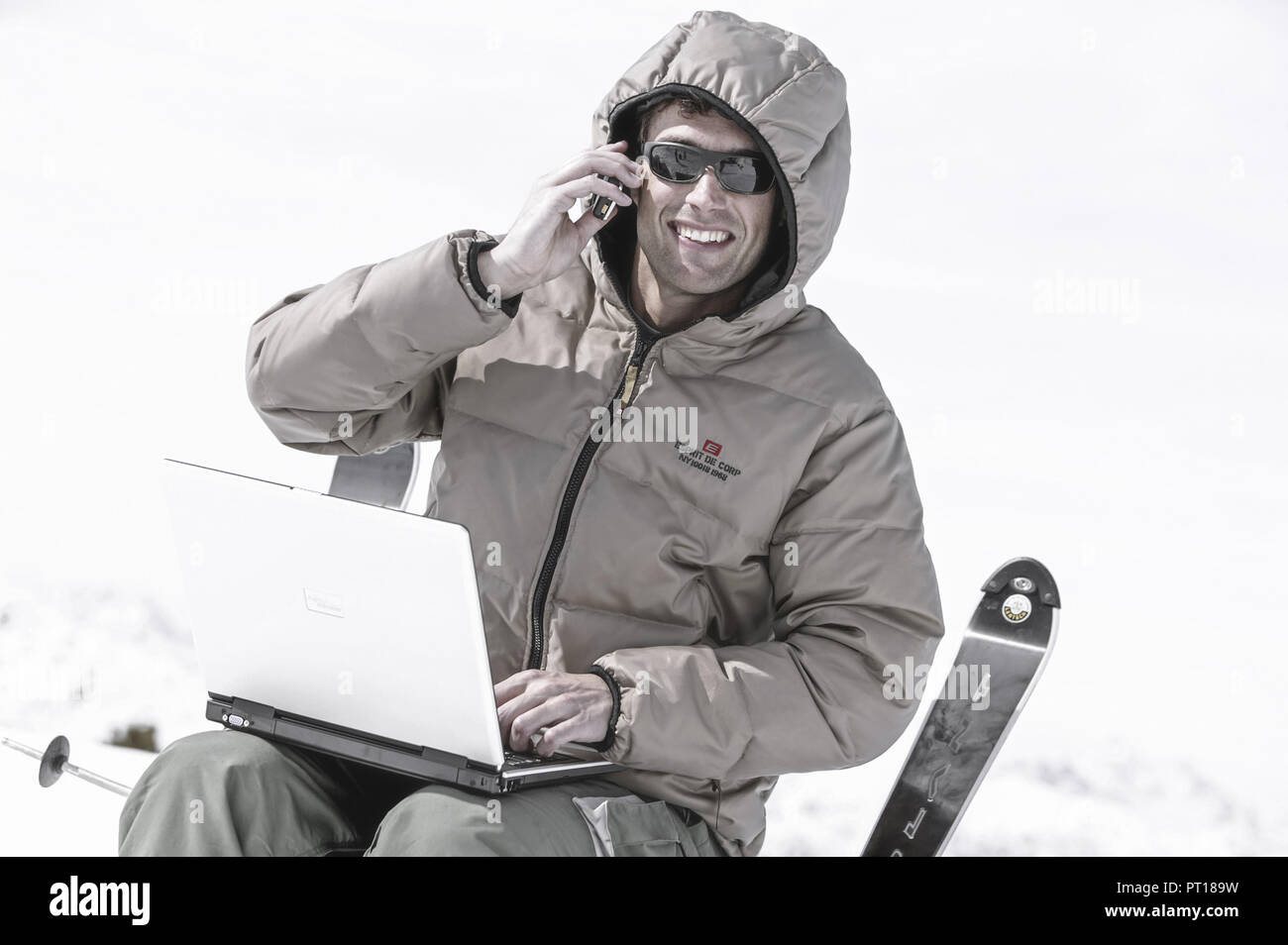man with laptop and mobile at winter holiday (model-released) - Stock Image