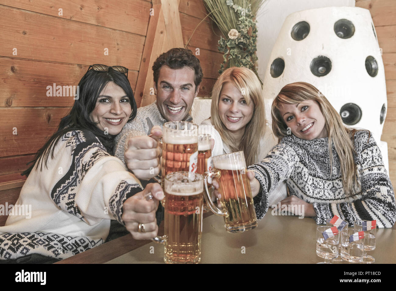 young people celebrating apres ski at ski hut (model-released) - Stock Image