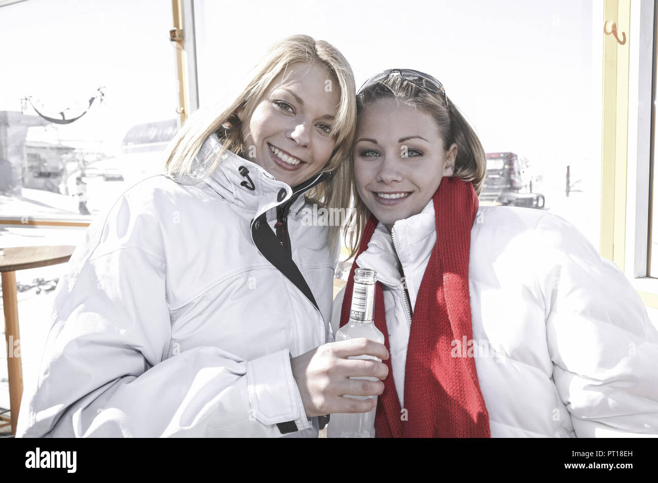 two women drinking alkopops at a skibar (model-released) - Stock Image