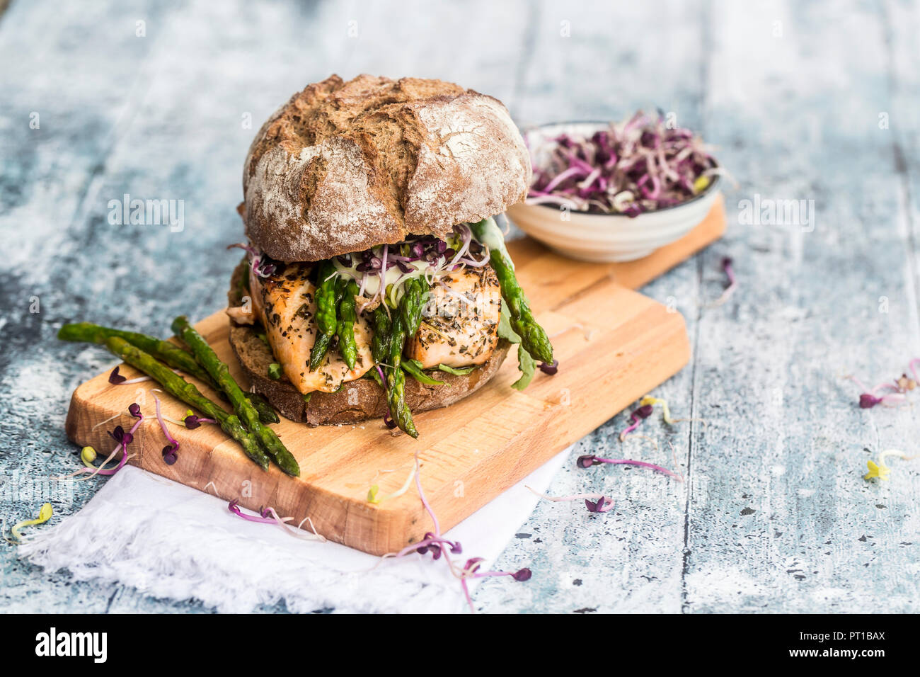 Salmon burger with green asparagus and red cress on chopping board - Stock Image