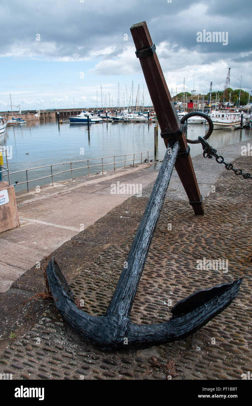 Huge metal traditional anchor laying on a cobble quayside overlooking a harbour on a clear and sunny day. - Stock Image