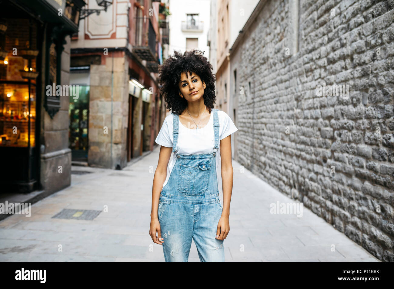 Spain, Barcelona, portrait of woman with curly hair wearing dungarees - Stock Image