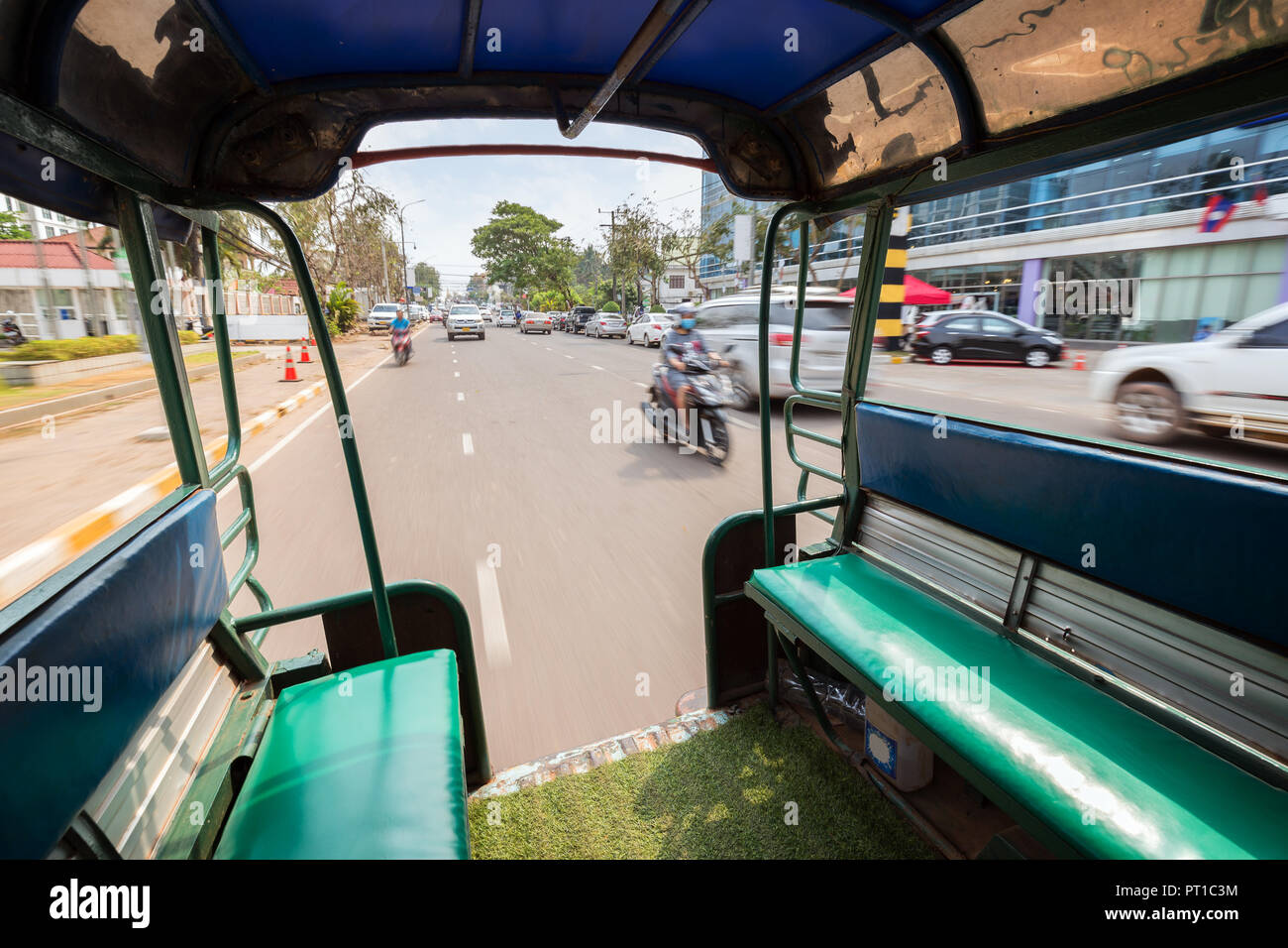 View of traffic on a street from the back of a songthaew (pick-up or small truck with benches along the sides) in Vientiane, Laos, on a sunny day. - Stock Image