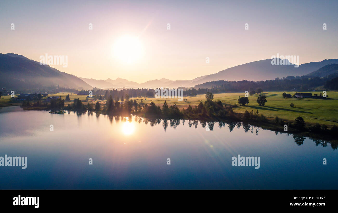 Austria, Tyrol, Kaiserwinkl, Aerial view of lake Walchsee at sunrise - Stock Image