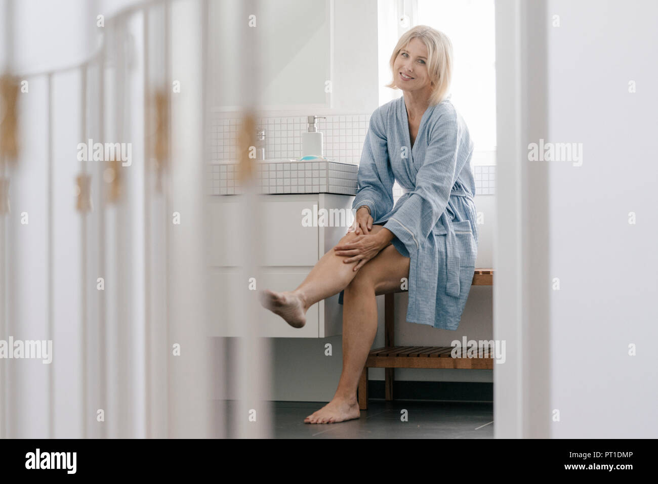 Mature women legs Portrait Of Smiling Mature Woman Sitting In Bathroom Touching Her Legs Stock Photo Alamy