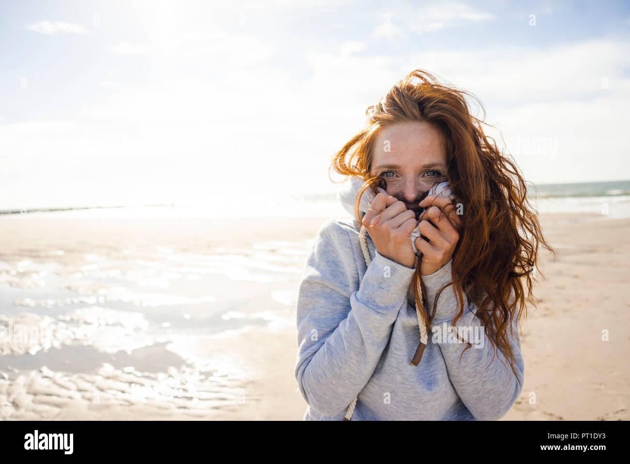 Redheaded woman enjoying fresh air at the beach - Stock Image