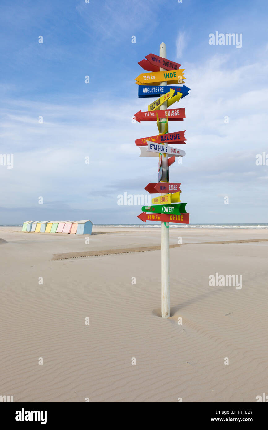 Signpost with directions to international locations at the beach of Berck-Plage, France, colorful beach cabins in background. Stock Photo