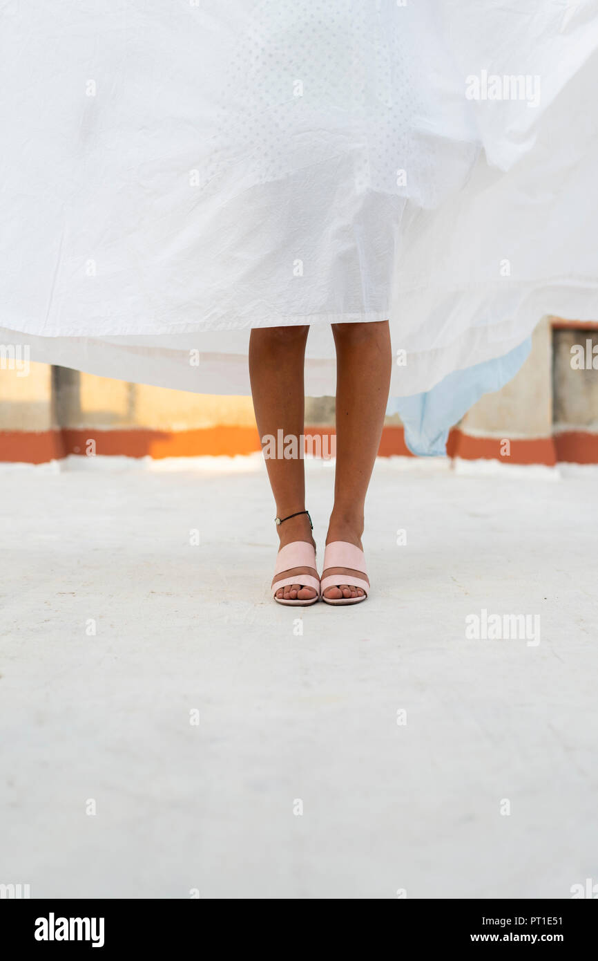 Legs of young woman hiding behind drying bed sheet - Stock Image