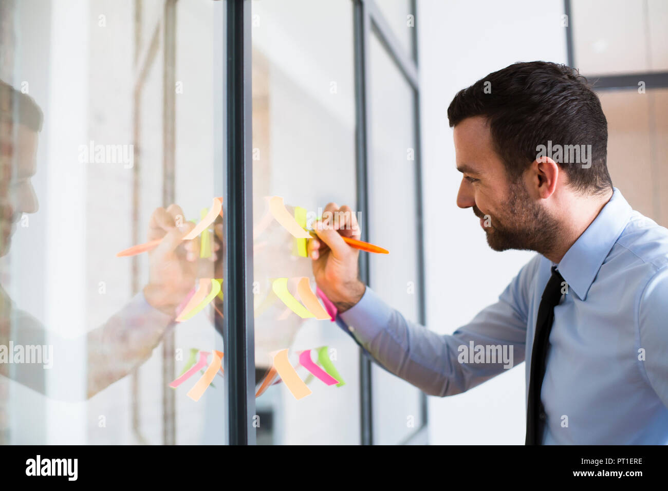 Businessman in office writing on adhesive note on glass wall - Stock Image