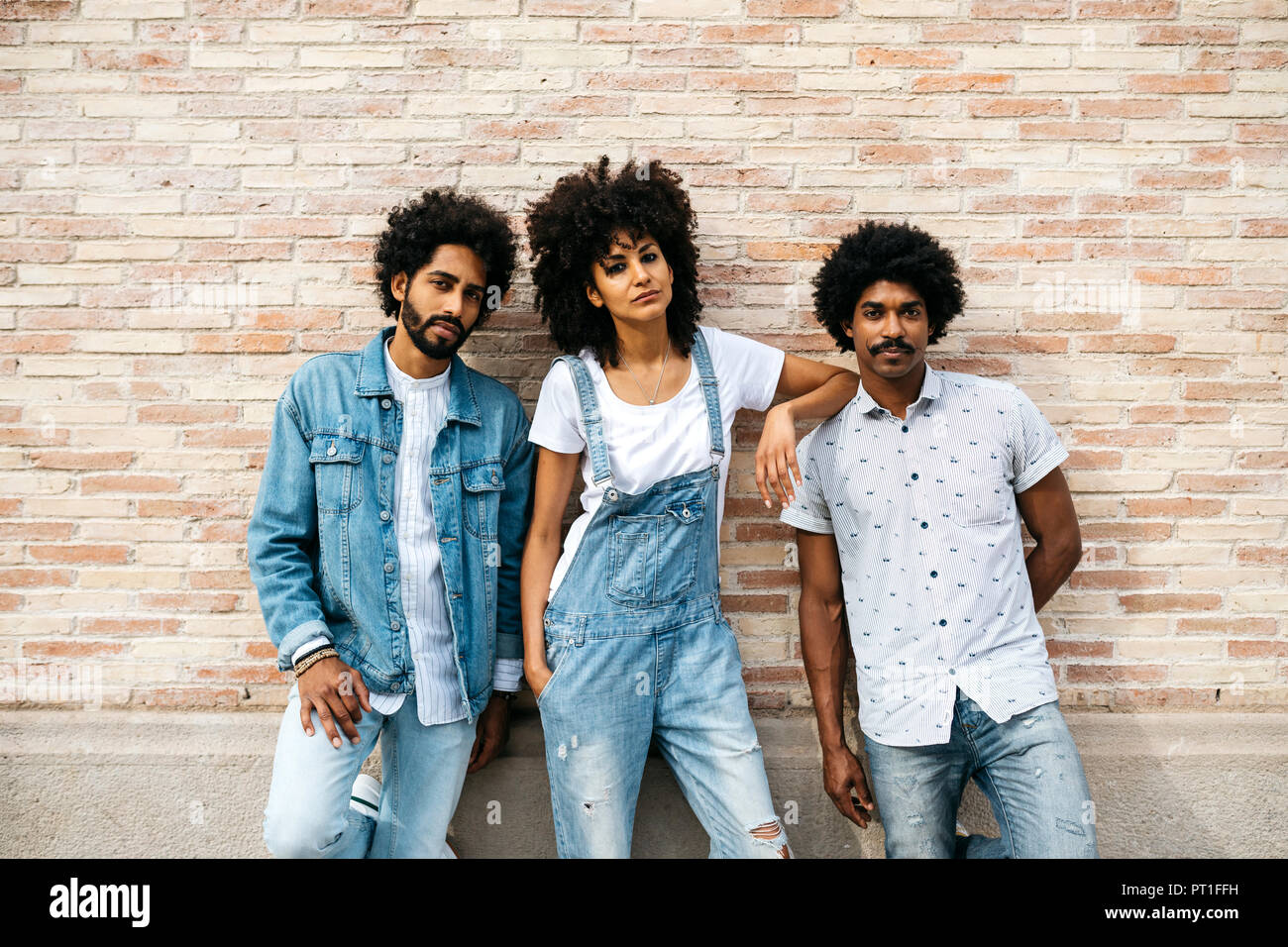 Portrait of three friends wearing denim standing in front of brick wall - Stock Image