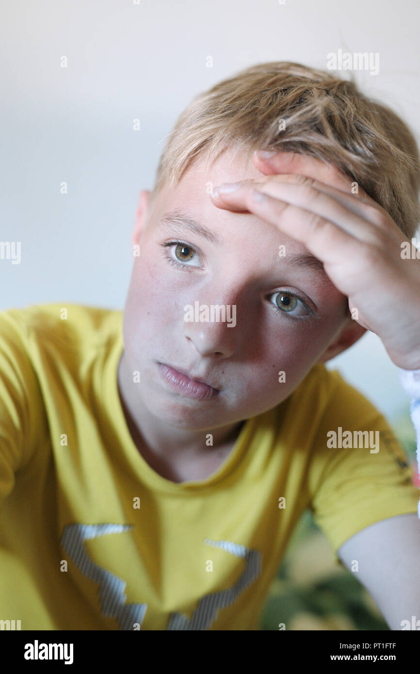 Portrait of pensive blond boy wearing yellow t-shirt - Stock Image