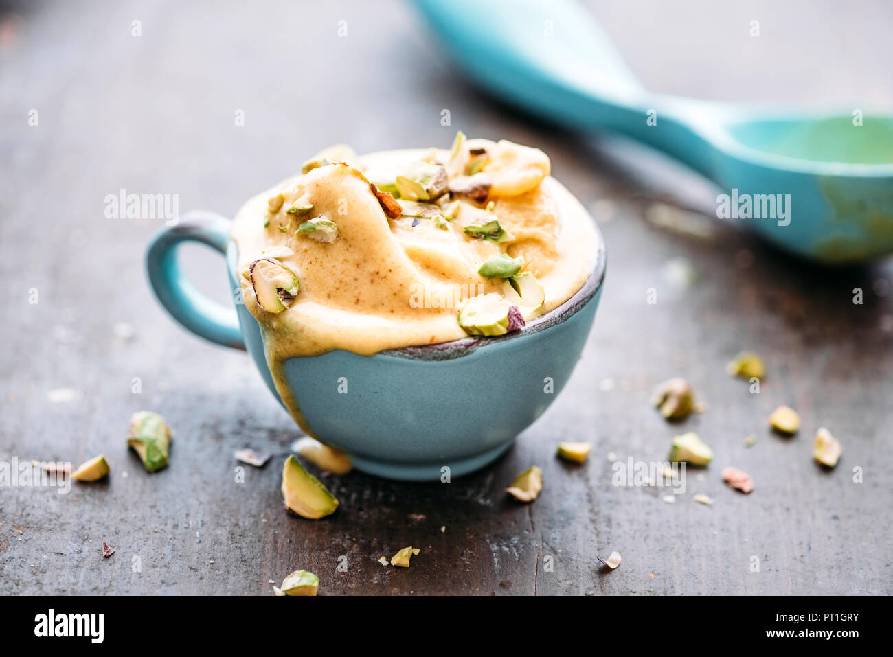 Homemade saffron ice cream with pistachio nuts, melting - Stock Image