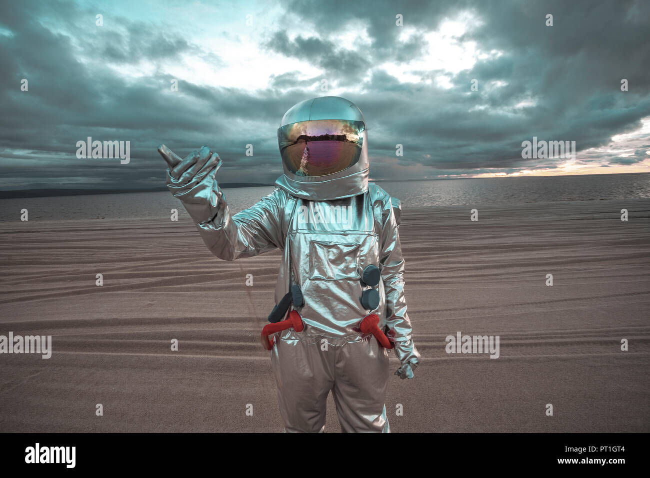 Spaceman pointing at something on a nameless planet - Stock Image