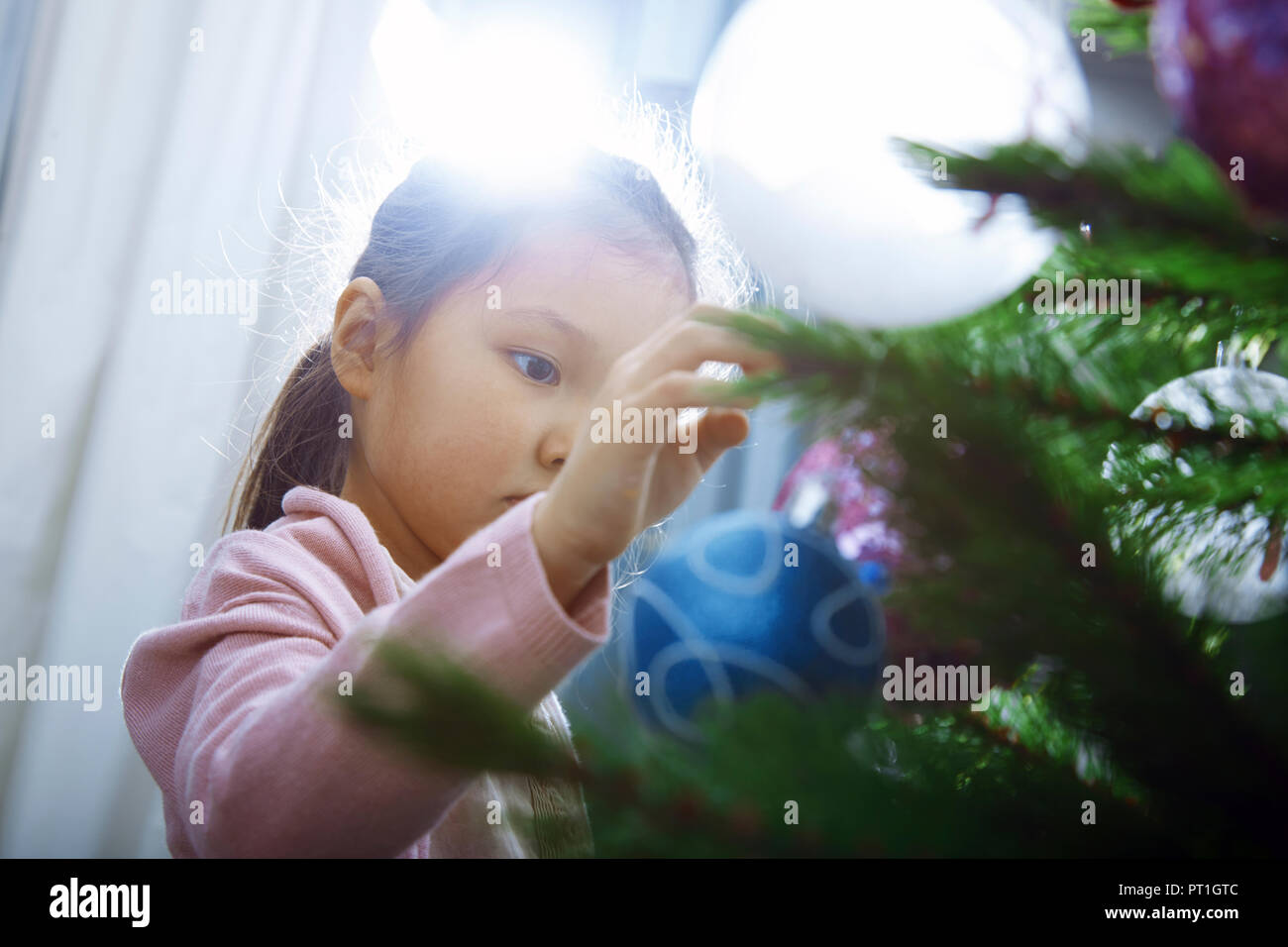 Little girl decorating Christmas tree - Stock Image