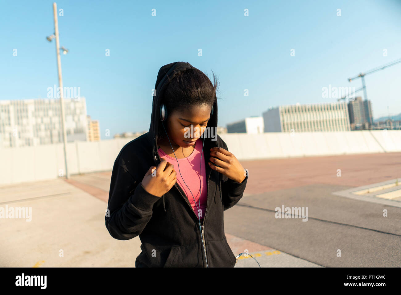 Young sportive woman listening music with headphones - Stock Image