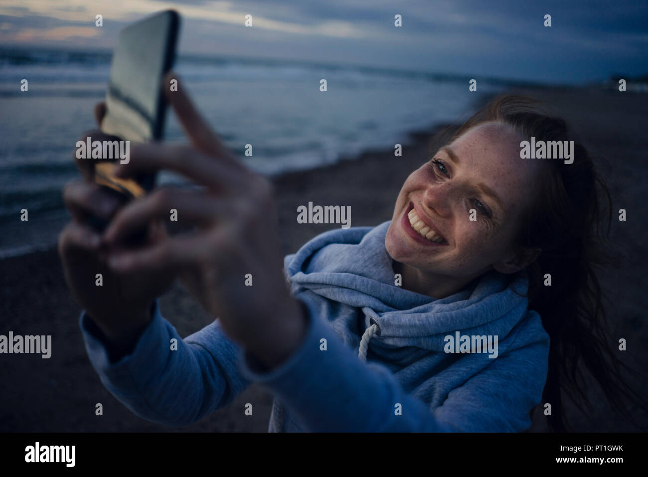 Woman using smartphone on the beach at sunset Stock Photo