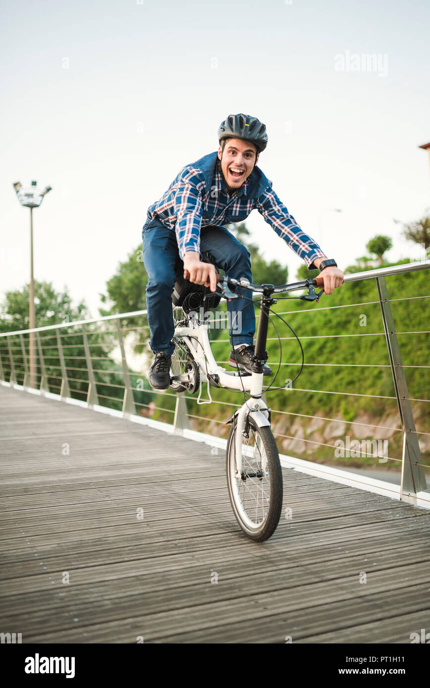 Young man doing tricks with a folding bike Stock Photo