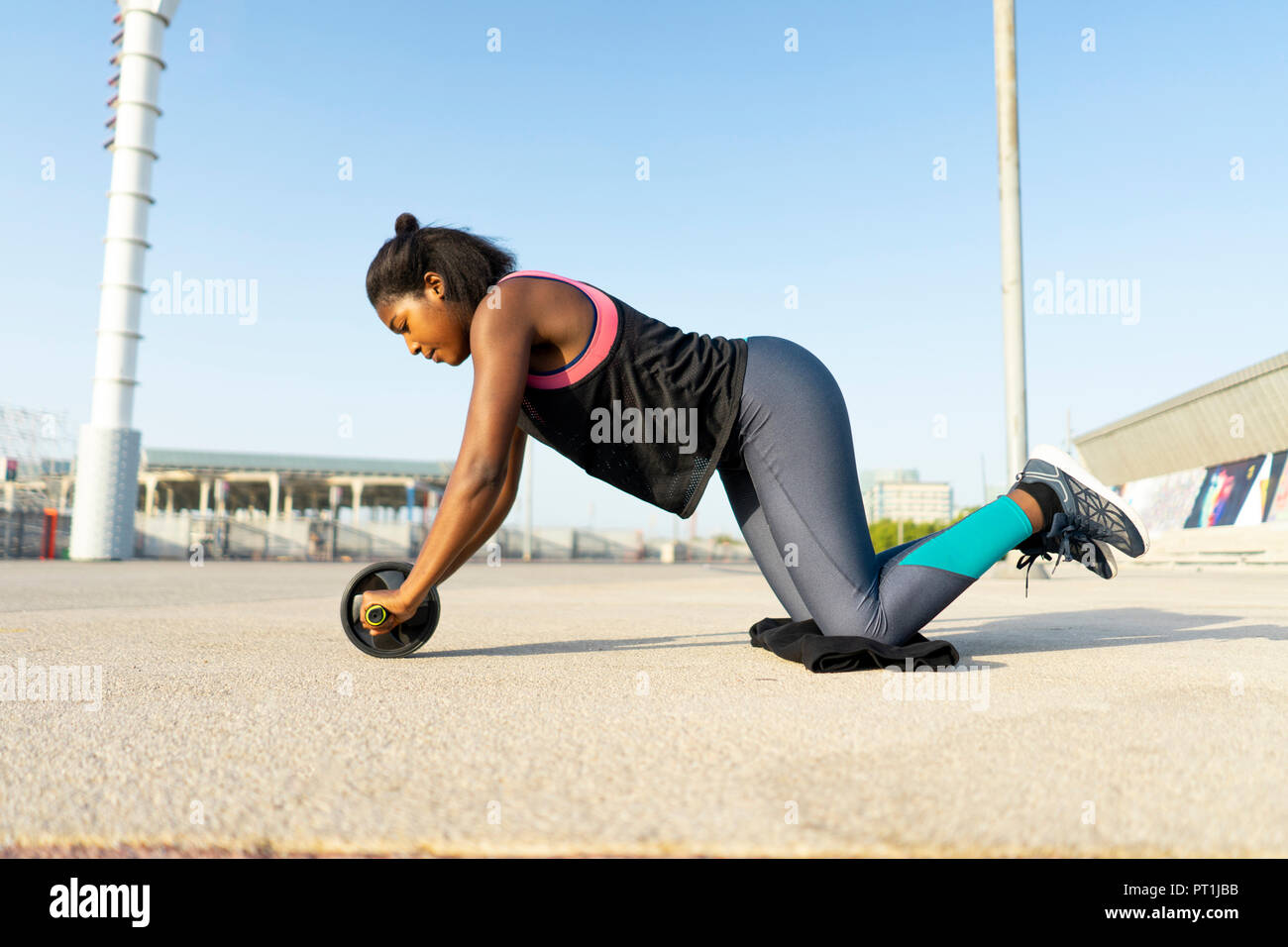 young sportive woman training with an ab wheel - Stock Image