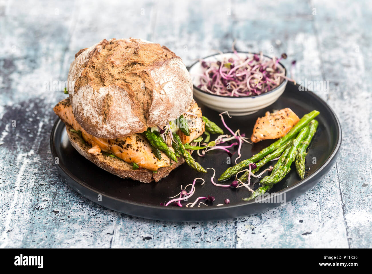 Salmon burger with green asparagus and red cress on plate - Stock Image