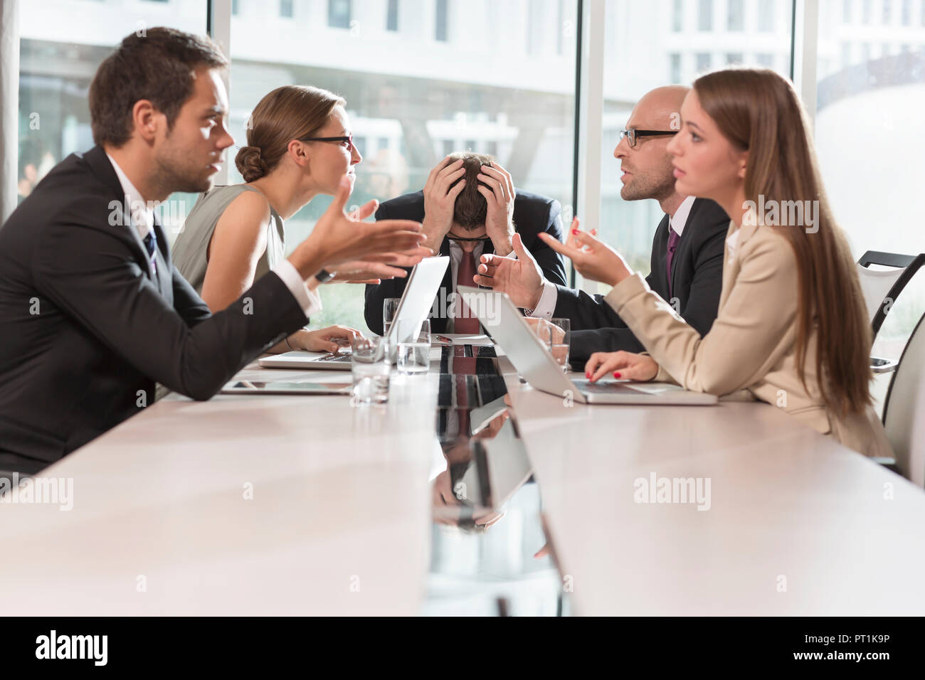 Five business people having an argument - Stock Image
