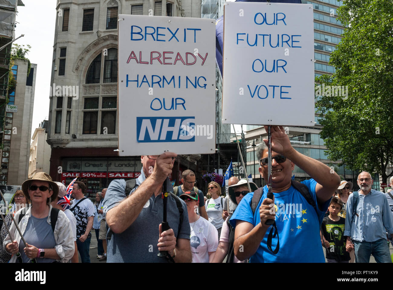 Two smiling men on Anti-Brexit rally in support of second referendum, carrying placards 'Brexit already harming our NHS' and 'Our future our vote' - Stock Image