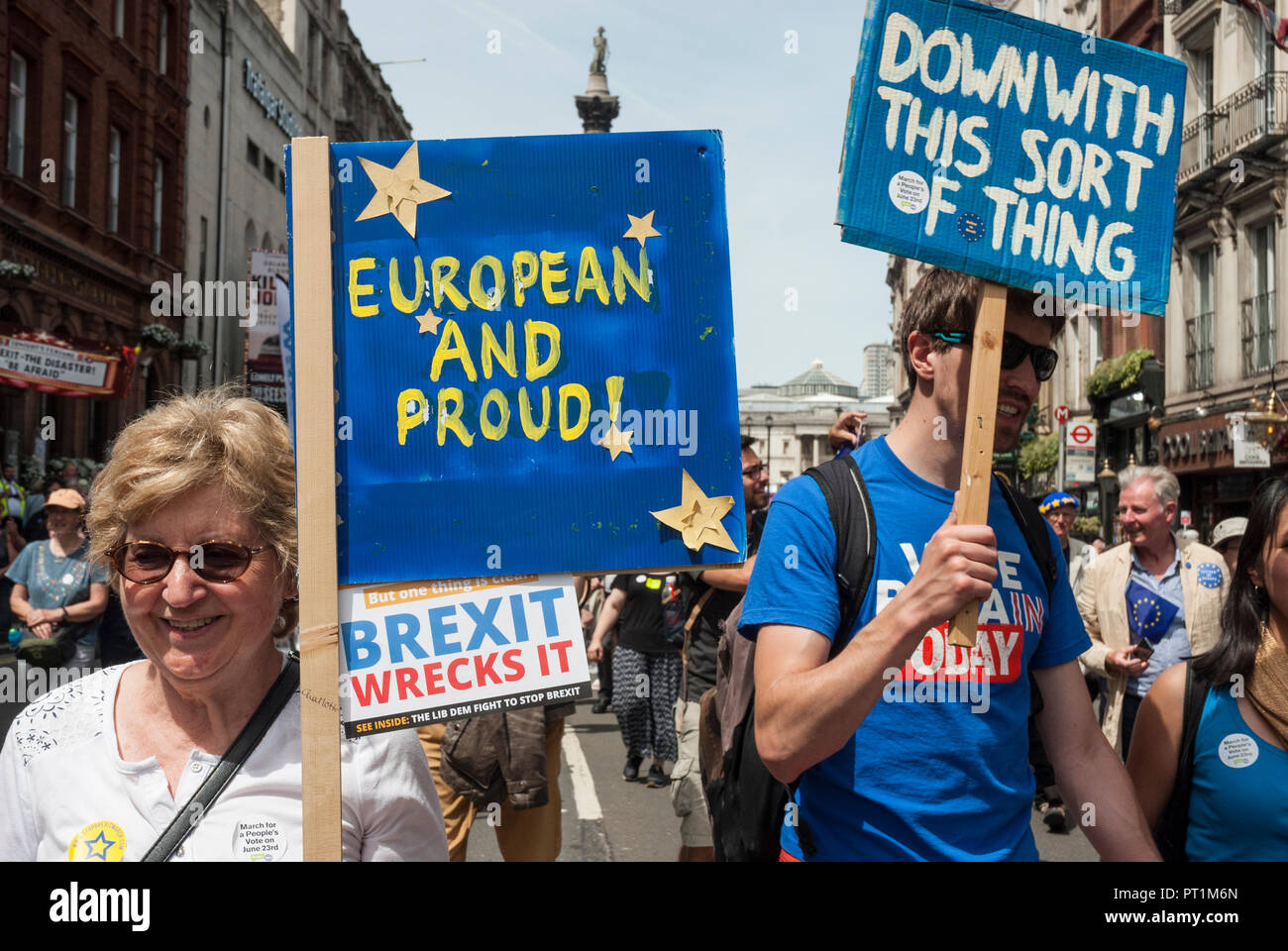 Anti Brexit rally with smiling woman and young man carrying placards 'European and proud!' and 'Down with this sort of thing'. - Stock Image
