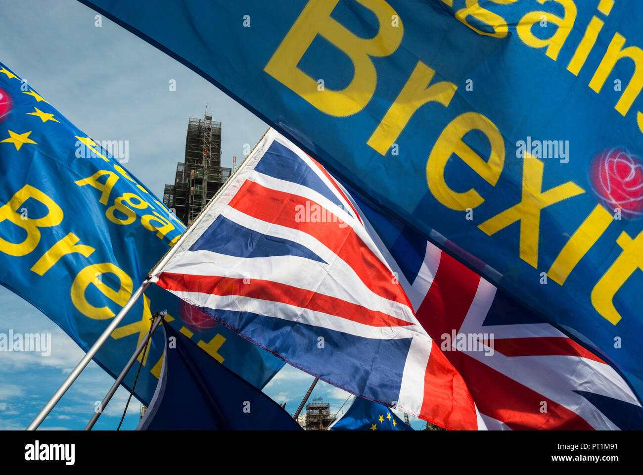Colourful flags, blue with yellow writing and stars 'Against BREXIT' next to Union Jack. Sunshine. - Stock Image