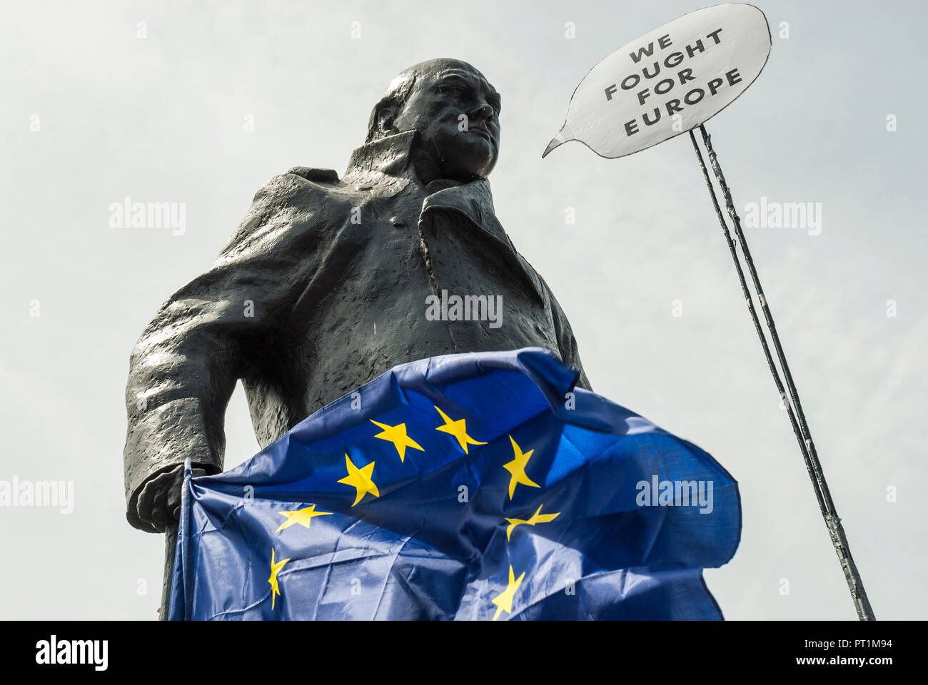 Statue of Sir Winston Churchill located outside Parliament holding an EU flag (blue with gold stars) with a speech bubble 'We fought for Europe' - Stock Image