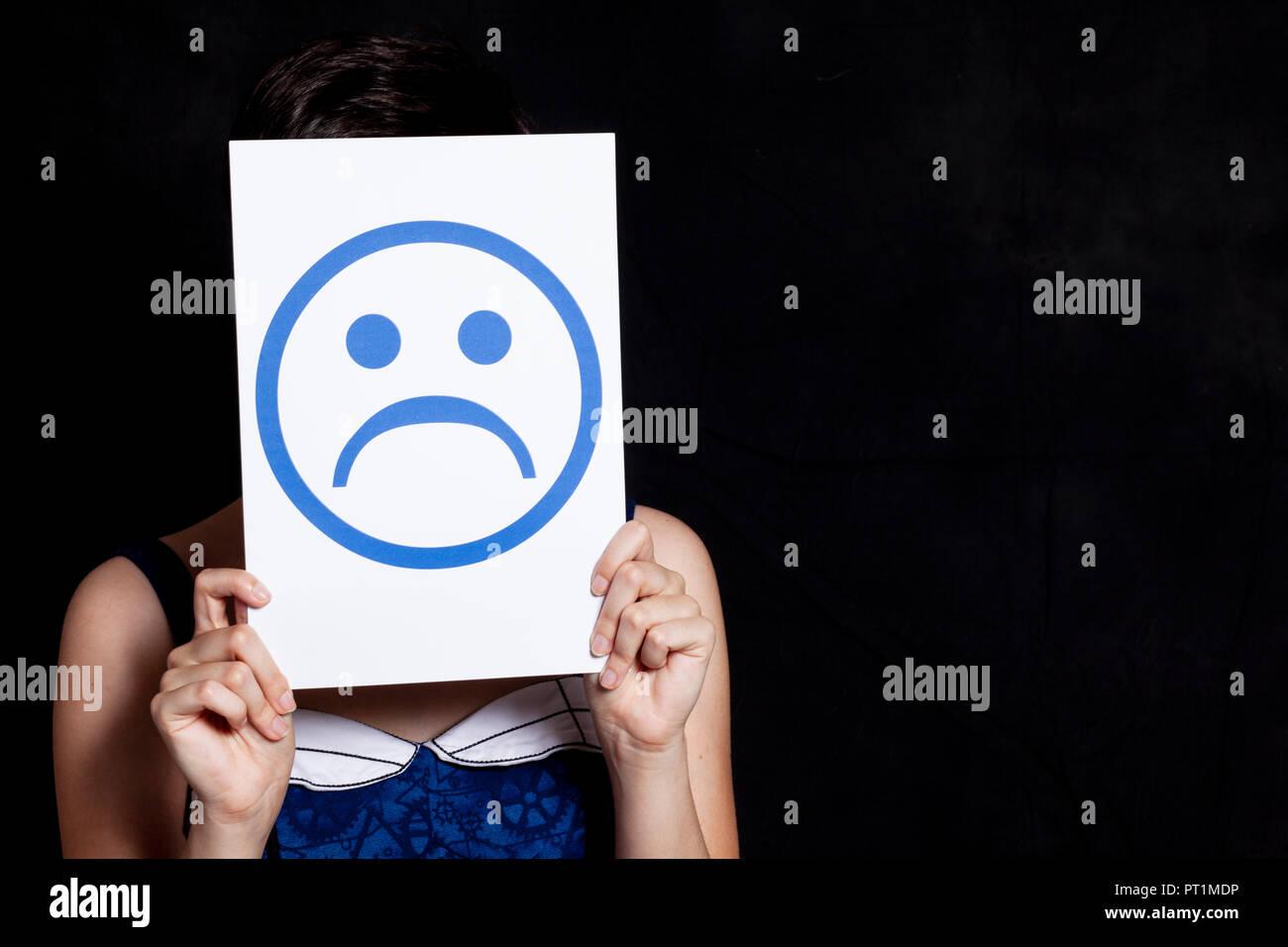 woman holding emoticon - sadness - black background - Stock Image