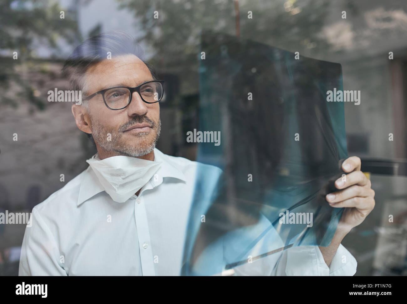 Portrait of radiologist behind windowpane looking at x-ray image - Stock Image