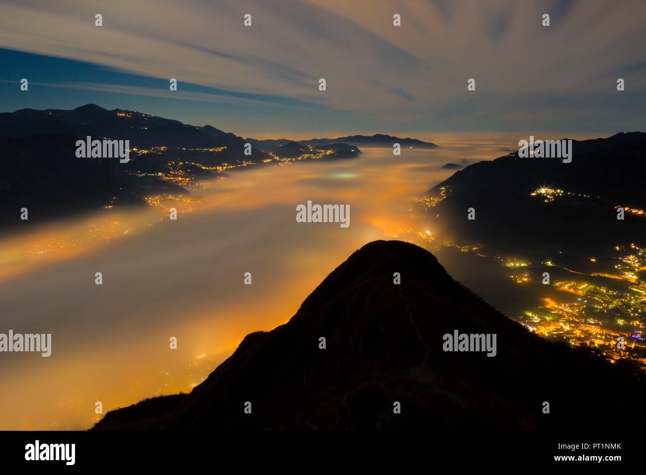 Fog bank illuminated from the lights of the cities below viewed from the top of Barro mount, Barro mount Regional Park, Lecco province, Lombardy, Italy - Stock Image