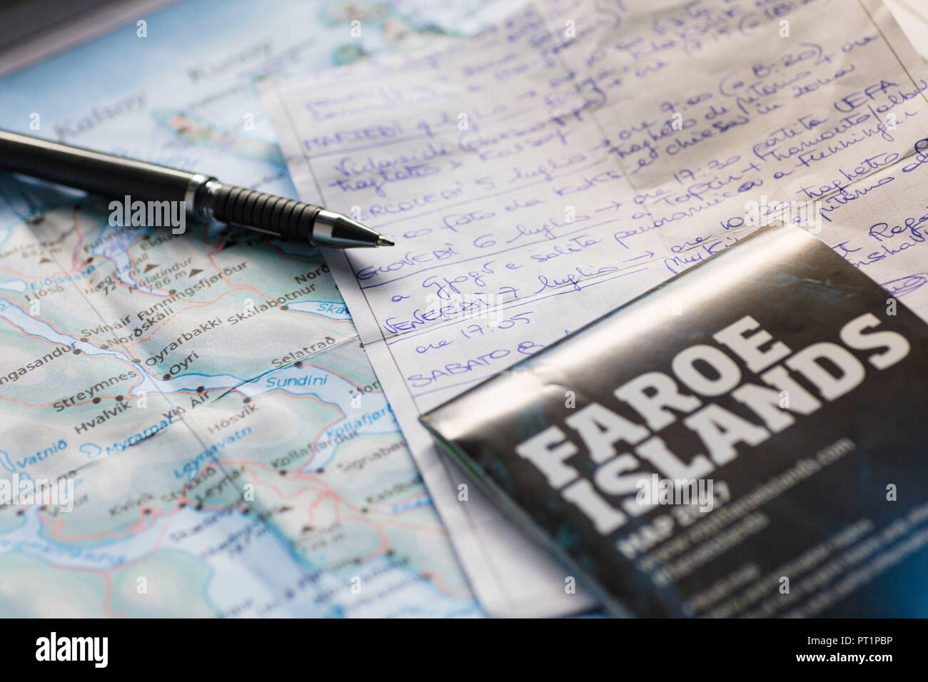 Notes and map of Faroe Islands on table for scheduling the trip - Stock Image