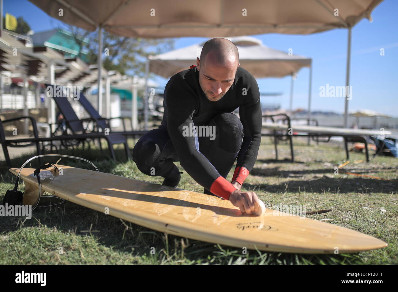 Sochi, Russia. 05th Oct, 2018. A surfer waxes a shortboard at the 2018 Russian Surfing Championships at the Khosta Rika surfing spot on the Black Sea coast. Sergei Bobylev/TASS Credit: ITAR-TASS News Agency/Alamy Live News - Stock Image