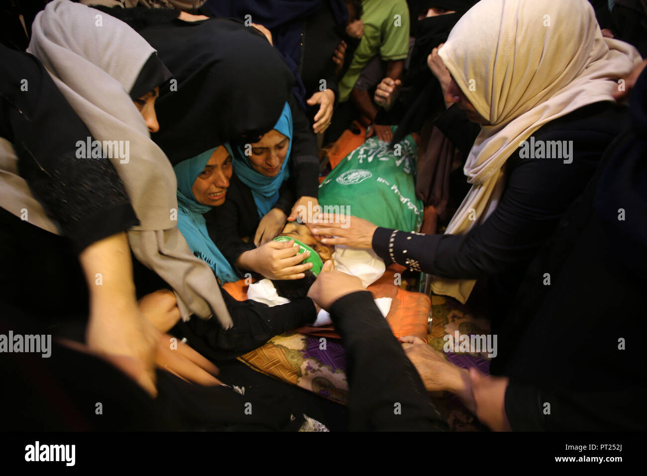 Gaza City, Gaza Strip, Palestinian Territory. 5th Oct, 2018. Relatives of Palestinian boy Faris al-Sersawi, 12, who was shot dead by Israeli froces during clashes in tents protest where Palestinians demand the right to return to their homeland at the Israel-Gaza border, mourn over his body during his funeral in Gaza City on October 6, 2018 Credit: Dawoud Abo Alkas/APA Images/ZUMA Wire/Alamy Live News - Stock Image