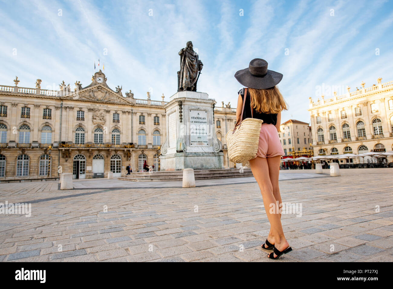 Young woman tourist enjoying beautiful morning view on the central square traveling in Nancy city in France Stock Photo