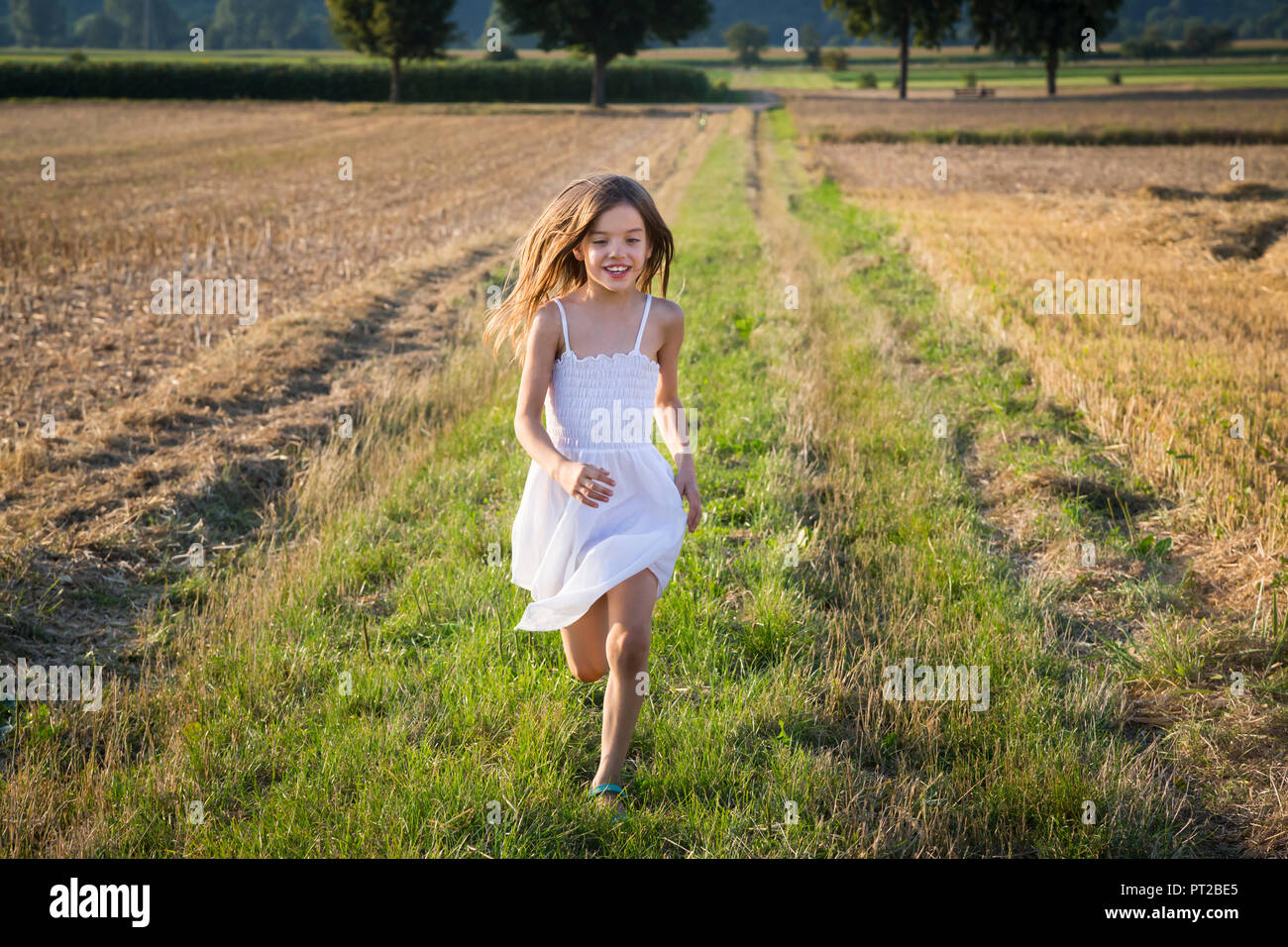 Happy little girl running in nature - Stock Image