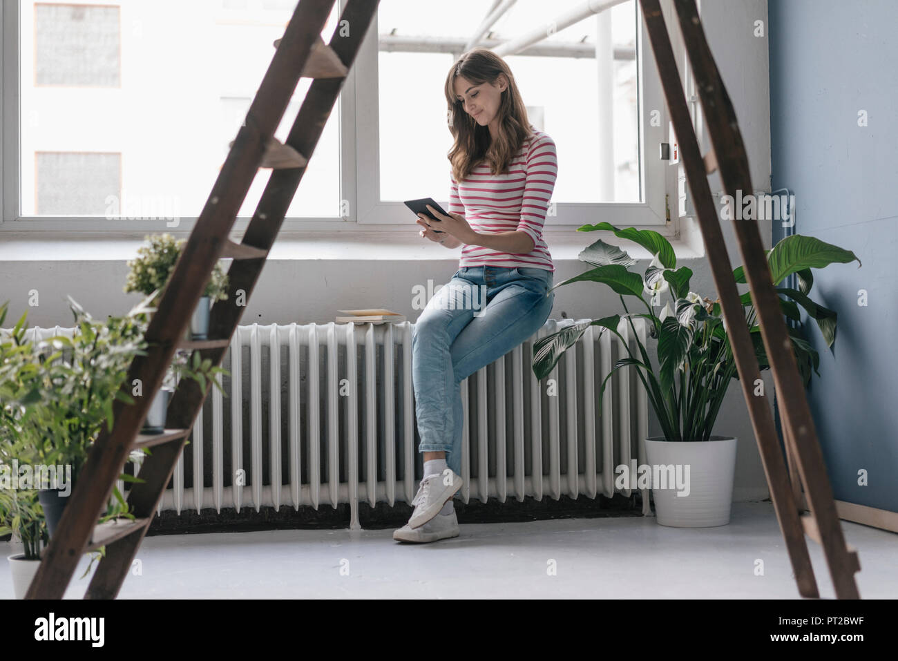 Woman sitting on radiator in her new home, reading e-book, surrounded by plants Stock Photo