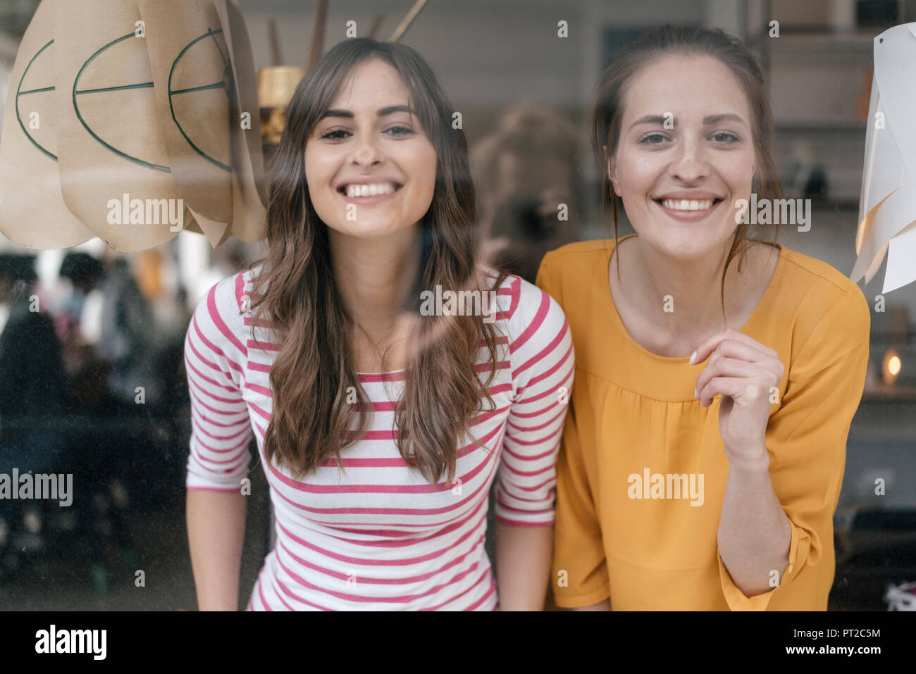 Friends pressing noses against window - Stock Image