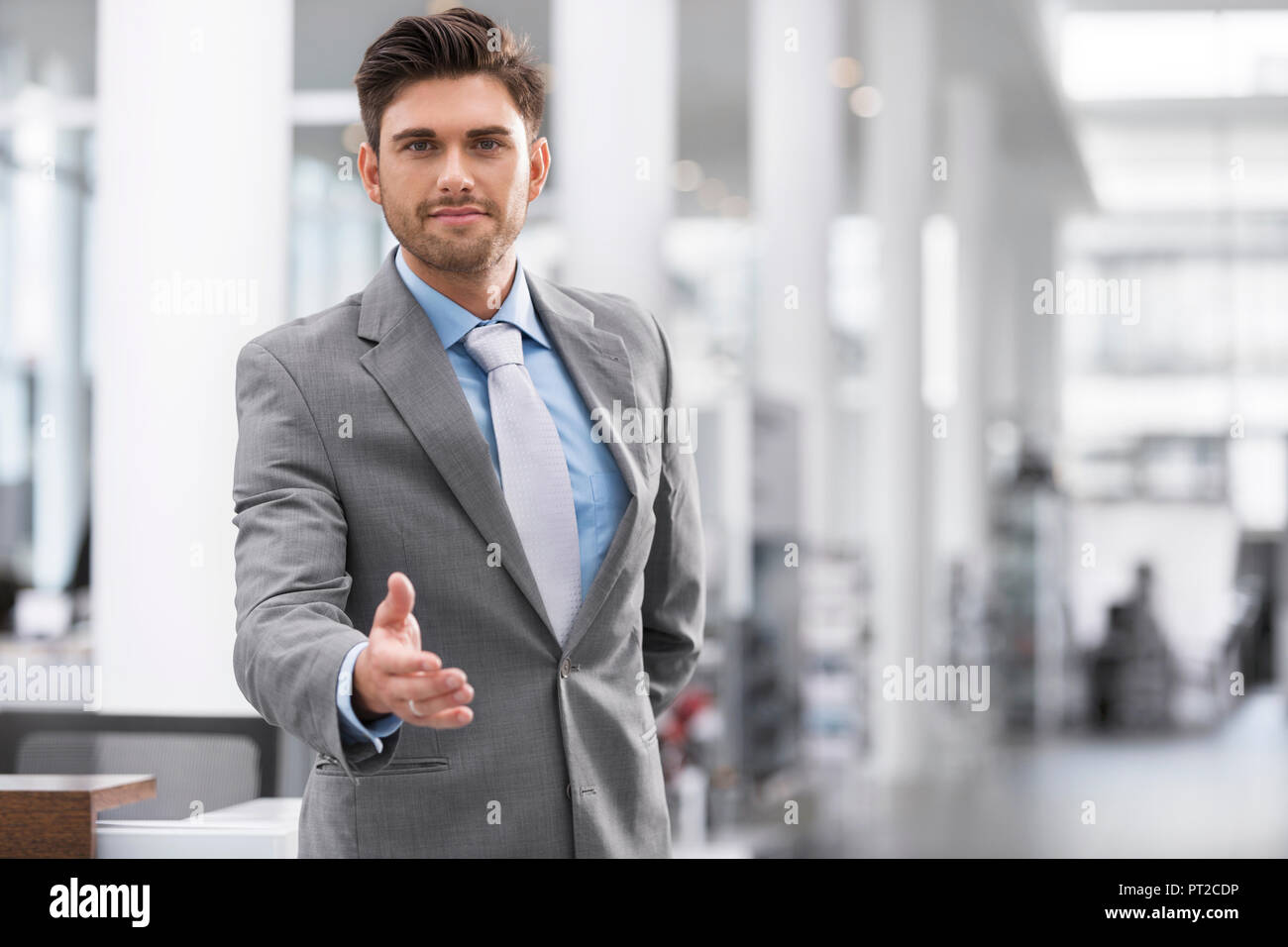 Businessman reaching out his hand - Stock Image