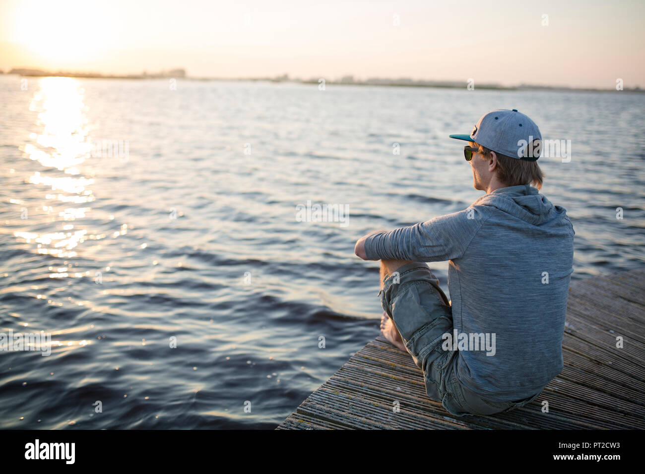 Man sitting on wooden boardwalk, enjoying sunset - Stock Image