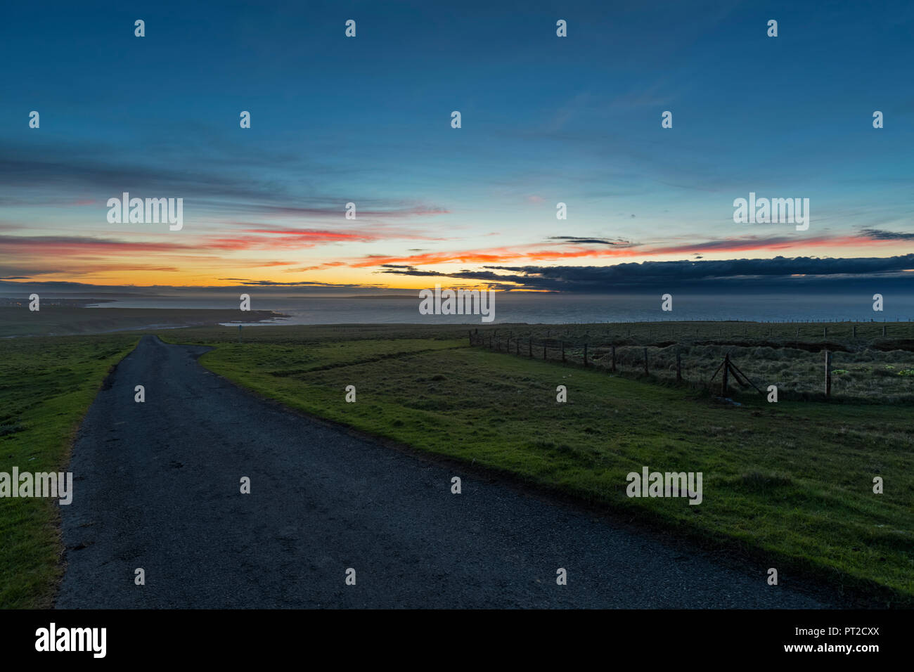 UK, Scotland, Caithness, Duncansby Head, rural road at sunset - Stock Image