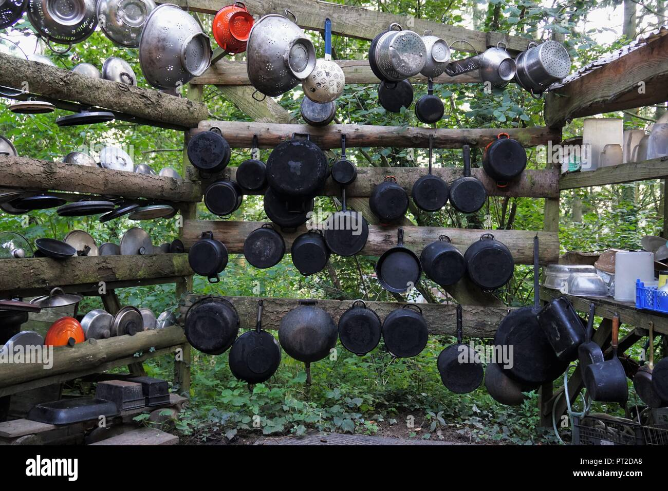 A huge assortment of pots and pans are ready to be used for cooking in a large forest camp. - Stock Image