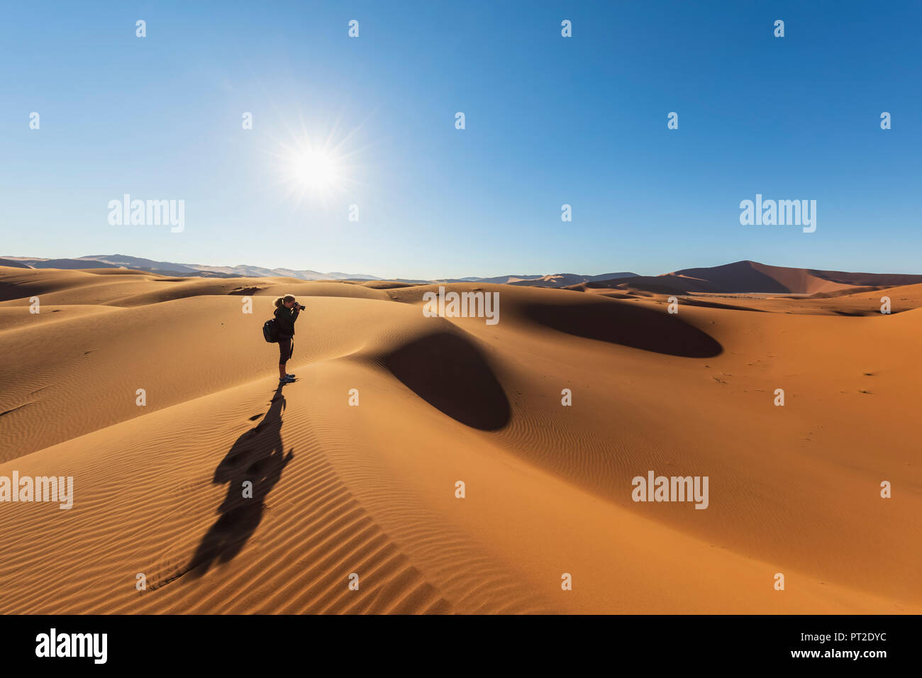 Africa, Namibia, Namib desert, Naukluft National Park, female photograper on sand dune against the sun - Stock Image