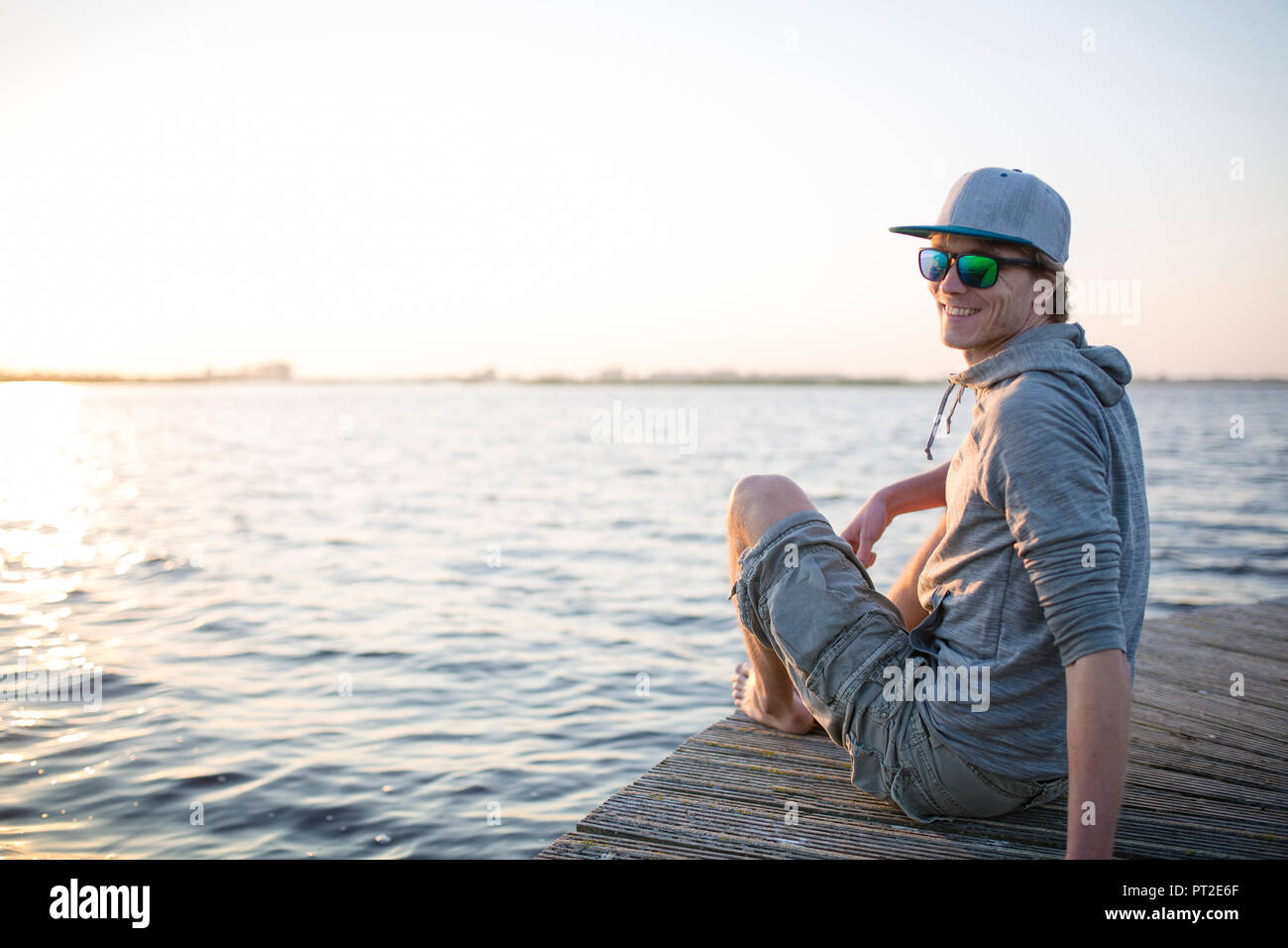 Smiling man sitting on wooden boardwalk at sunset - Stock Image